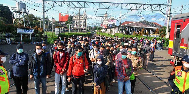 Sejumlah penumpang KRL Commuter Line antre menunggu kedatangan kereta di Stasiun Bogor, Jawa Barat, Senin (13/4/2020). Antrean panjang penumpang KRL Commuter Line di Stasiun Bogor tersebut akibat kebijakan pemeriksaan suhu tubuh dan pembatasan jumlah penumpang di setiap rangkaian kereta sebagai tindakan pencegahan penyebaran wabah pandemi virus Corona (COVID-19).