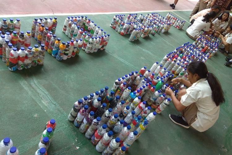 Siswa SMA Katolik Hikmah Mandala sedang membuat huruf yang terbuat dari rangkaian ecobrick, yaitu penanganan sampah plastik dengan menguncinya di dalam botol plastik bekas, Rabu (21/2/2018).
