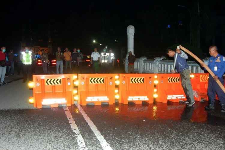 Petugas melakukan pengalihan jalur saat penutupan sebagian jalan protokol Kota Tegal, Jawa Tengah, Senin (22/3/2020) malam. Pemerintah Kota Tegal dan Polres Tegal hingga 14 hari mendatang melakukan lockdown lokal dengan menutup jalur Pantura yang melintasi Kota Tegal, akses masuk Alun-alun Tegal dan mematikan sebagian lampu jalan protokol guna pembatasan kendaraan yang akan masuk ke Kota Tegal dan mencegah adanya kerumunan massa di jalan untuk mencegah penyebaran COVID-19. ANTARA FOTO/Oky Lukmansyah/aww.