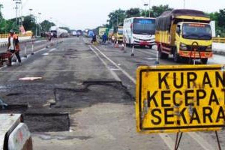 Sejumlah pekerja tengah memperbaiki jalan rusak di Jembatan Elon, Kabupaten Pemalang, Selasa (28/1/2014). Jalan rusak tak hanya terdapat di sepanjang jalan Pantura Barat. Namun, di sejumlah jembatan pun terdapat aspal yang mengelupas.