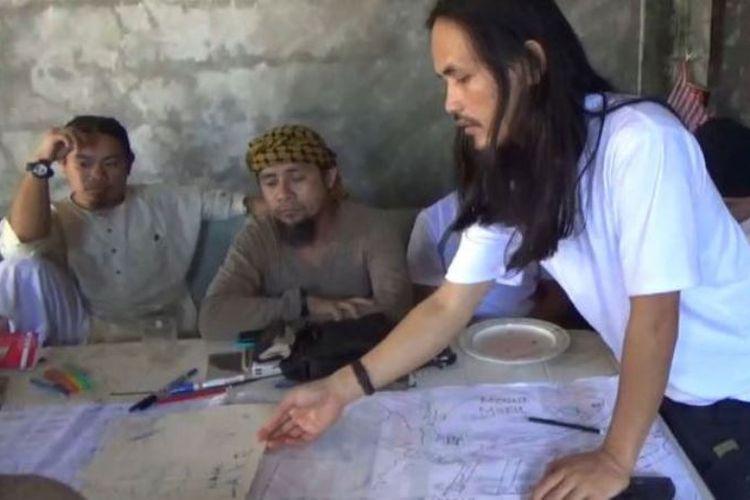 Abdullah Maute (berdiri) menunjuk peta dalam pertemuan dengan Isnilon Hapilon (kedua dari kiri), yang merupakan pemimpin kelompok Abu Sayyaf. Foto ini didapat militer Filipina.