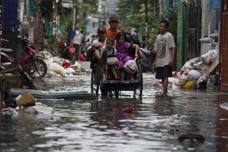 Sejumlah warga melintasi jalan yang tergenang banjir di wilayah Teluk Gong, Penjaringan, Jakarta Utara, Sabtu (4/1/2020).Hujan lebat di awal tahun membuat kawasan teluk gong masih terendam banjir.