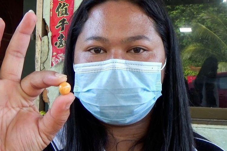 Kodchakorn Tantiwiwatkul, seorang wanita asal Thailand, menunjukkan mutiara Melo yang berwarna oranye setelah membukanya dari siput laut yang dibeli untuk makan siang. Mutiara itu bisa berharga hingga miliaran rupiah,
