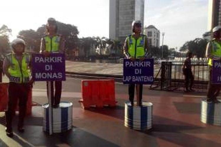Para polisi wanita membawa papan berisi imbauan parkir untuk buruh di Bundaran HI, Jumat (1/5/2015).