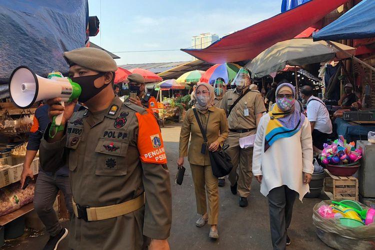 Sejumlah ASN dan Satpol PP bersama Manajer Area 11 Perumda Pasar Jaya, Cezania Nelsa berkeliling area Pasar Kebayoran Lama, Jakarta Selatan, Senin (6/7/2020). Aparatur Sipil Negara (ASN) hari ini mulai bertugas memantau kepatuhan masyarakat terhadap protokol kesehatan di sejumlah pasar di Jakarta Selatan, Senin (6/7/2020) pagi.