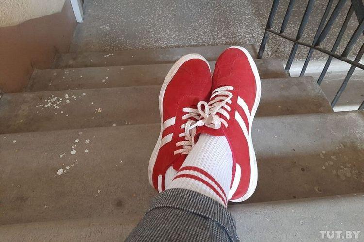 Natalia Sivtsova-Sedushkina memamerkan sepatu dan kaus kakinya yang berwarna merah putih sebelum ditangkap di Belarus. Dia ditahan karena mengenakan warna yang menjadi simbol oposisi Belarus.