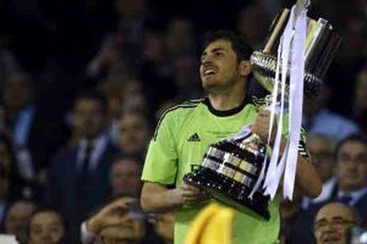 Kiper sekaligus kapten Real Madrid, Iker Casillas, mengangkat trofi Copa del Reya yang mereka sabet setelah menang 2-1 atas BArcelona pada partai final di Mestalla, Rabu (16/4/2014).