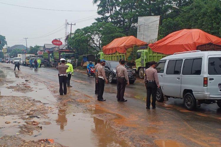 Pihak Kepolisian Polres Bogor sedang melakukan pembersihan jalan dan mengamankan barang bukti tanah galian ilegal di Cileungsi, Kabupaten Bogor, Jawa Barat, Kamis (5/11/2020).