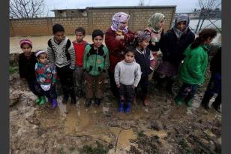 Pengungsi Suriah berkumpul karena tenda mereka kebanjiran akibat hujan, di kamp pengungsi sementara di kota Al-Faour, Lebanon Timur, dekat perbatasan Suriah, 8 Januari 2013.