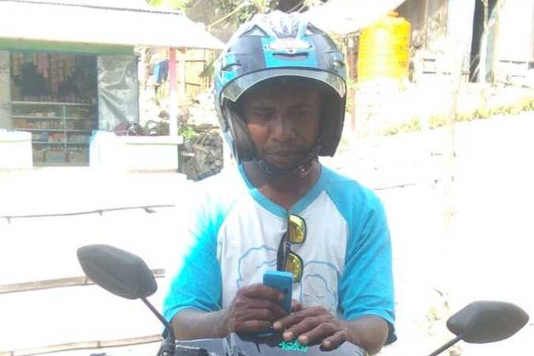 PHOTO:Maksi Foni (31), tukang ojek asal Desa Haumeni, Kecamatan Bikomi Utara, Kabupaten Timor Tengah Utara (TTU), Nusa Tenggara Timur, saat membaca pesan masuk di telepon genggamnya