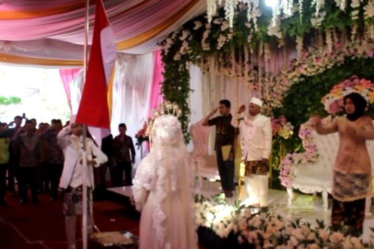 Calon pengantin Akhmad Muiz Maulana (22) dan Tyas Atikah (24) menjadi pengibar bendera upacara peringatan HUT RI sebelum prosesi akad nikah di Desa Kambangsari, Kecamatan Alian, Kabupaten Kebumen, Sabtu (17/8/2019).