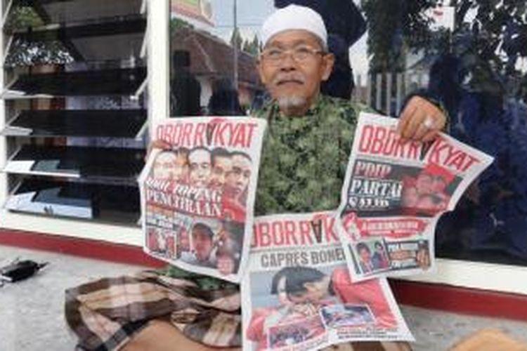 Pengasuh pondok pesantren Al Falah Kabupaten Jember, Jawa Timur, KH Imam Haramain, menunjukkan kiriman tabloid obor rakyat edisi pertama hingga ketiga, Selasa (17/6/2014)