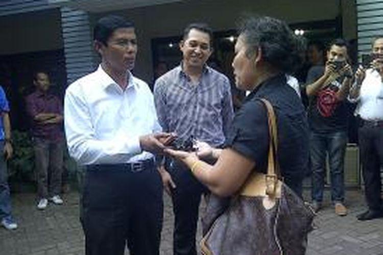 Direktur Kriminal Umum, Kombes Polisi Slamet Riyanto, dan pemilik mobil, Nilam Suryani, melakukan serah terima kunci di Mapolda Metro Jaya, Jakarta, Kamis (29/8/2013). Empat mobil milik Nilam Suryani dibawa lari mahasiswanya, Pendi Manalu.