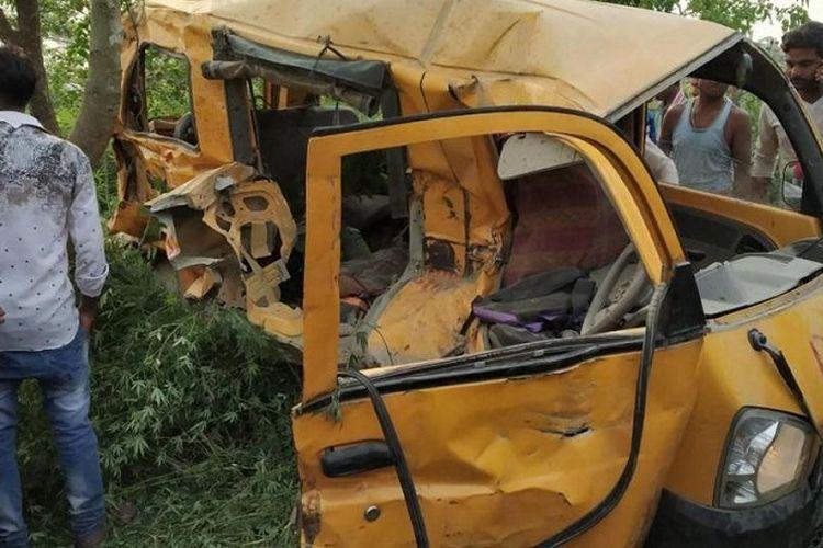 Warga di Kushinagar, India, mengerumuni van berwarna kuning yang bertabrakan dengan kereta Kamis waktu setempat (26/4/2018). Akibat insiden itu, 13 anak sekolah dilaporkan tewas.