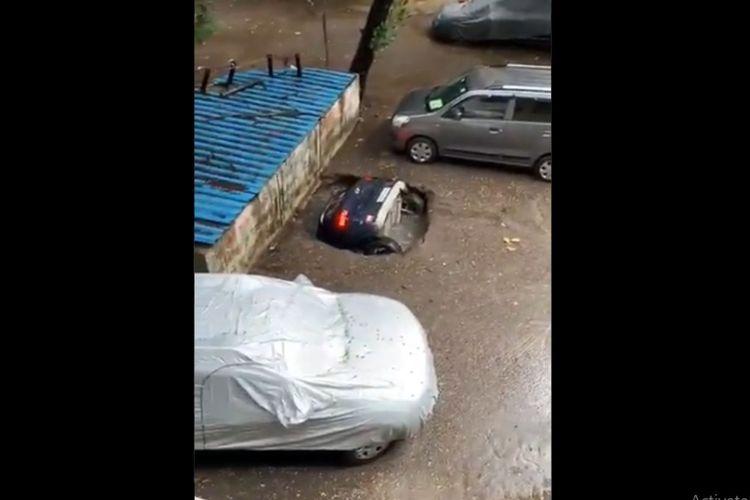 Mobil SUV tersedot dalam lubang yang tiba-tiba muncul di atas lahan parkir di Mumbai pada Minggu (13/6/2021). [SS/TWITTER/@thakur_shivangi]