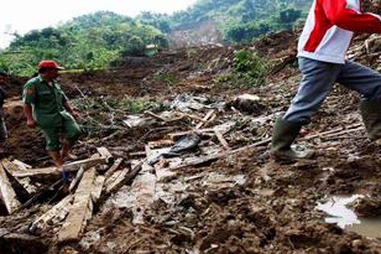 Beberapa perangkat desa membantu menyisir korban diantara longsoran Kampung Nagrog, Desa Mukapayung, Kecamatan Cililin, Kabupaten Bandung Barat, Jawa Barat, Senin (25/3/2013). Peristiwa longsor yang terjadi sekitar pukul 5.30 ini mengakibatkan 10 warga tewas, enam luka berat, dan 7 warga lain masih dalam pencarian karena masih tertimbun longsor.