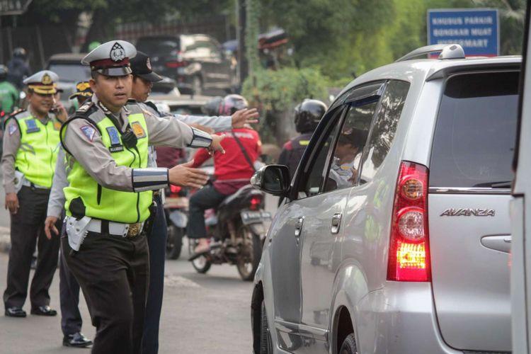 Sejumlah petugas kepolisian memberi arahan kepada pengendara mobil pada uji coba ganjil genap di ruas Tol Jagorawi, Jakarta, Senin (16/4/2018). Uji coba yang dilakukan setiap hari Senin-Jumat kecuali hari libur nasional tersebut dimulai pukul 06.00 hingga 09.00 WIB diharapkan dapat mengurai kemacetan.