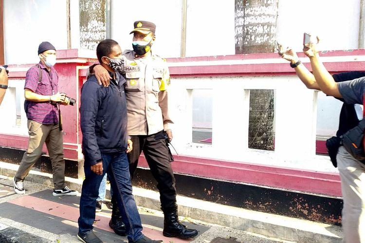 Polisi mengamankan pria pembentang poster ke arah Jokowi di Jalan Moh Hatta, Kota Blitar, Selasa (7/9/2021)