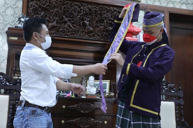 Ganjar Pranowo ketika menerima satu set baju adat Tobelo, Maluku Utara yang diserahkan oleh Toni Pulo secara langsung di Puri Gedeh, Kota Semarang. Sabtu (11/9/2021).