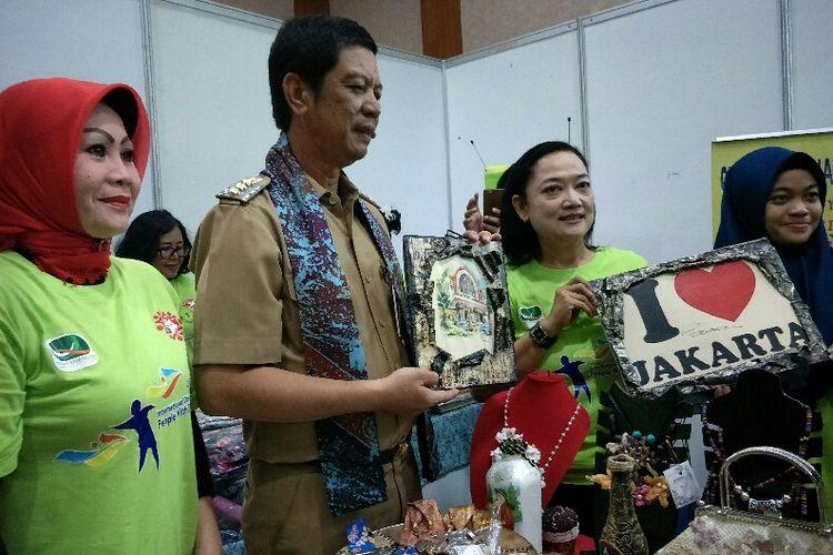 Wali Kota Jakarta Barat Rustam Effendi (tengah) berbelanja hasil karya anak disabilitas dalam stan pameran pada peringatan Hari Disabilitas pada Selasa (4/12/2018).