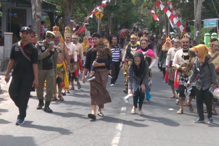 Bupati Trenggalek Mochammad Nur Arifin (gendong anak) turut berjalan bersama peserta pawai budaya nusantara. Sedangkan sang istri memungut sampah di jalan yang dilaluinya (03/08/2019)