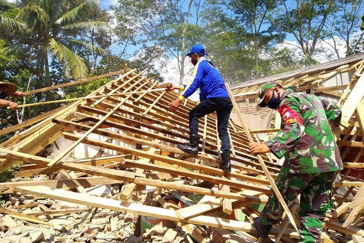 Warga, anggota Banser, dan warga membersihkan puing-puing bangunan rumah warga di Desa Tepas, Kecamatan Kesamben, Kabupaten Blitar, Rabu (14/4/2021), yang rusak berat akibat gempa bumi pekan lalu.