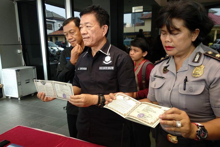 Kasat Reskrim Polres Metro Bekasi Kota Jairus Saragih menunjukkan barang bukti BPKB kendaraan pada kejahatan fiducia, Selasa (15/5/2018)
