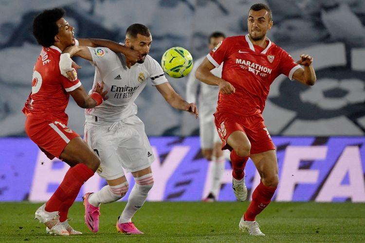 Striker Real Madrid, Karim Benzema, berebut bola dengan pemain Sevilla Jules Kounde dan Jordan Moreno dalam laga Liga Spanyol 2020-2021 di Stadion Alfredo Di Stefano, 9 Mei 2021.