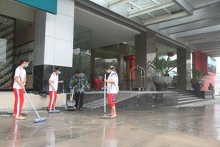 Sejumlah pegawai hotel membersihkan abu vulkanis gunung Kelud yang menempel di area hotel, Sabtu (15/2/2014).