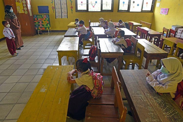 Guru membimbing sejumlah siswa saat mengikuti proses belajar mengajar tatap muka terbatas di SD Negeri Pejaten I di Kramatwatu, Serang, Banten, Senin (23/8/2021). Pemerintah setempat secara selektif memberi izin bagi sekolah-sekolah di zona hijau memberlakukan pembelajaran tatap muka dengan pembatasan separuh dari kapasitas kelas serta penerapan protokol kesehatan. ANTARA FOTO/Asep Fathulrahman/wsj.