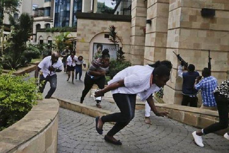 Warga sipil kompleks hotel di Nairobi, Kenya, menunduk sembari melarikan diri dengan pasukan keamanan (kanan) menembak ketika serangan terjadi pada Selasa (15/1/2019).
