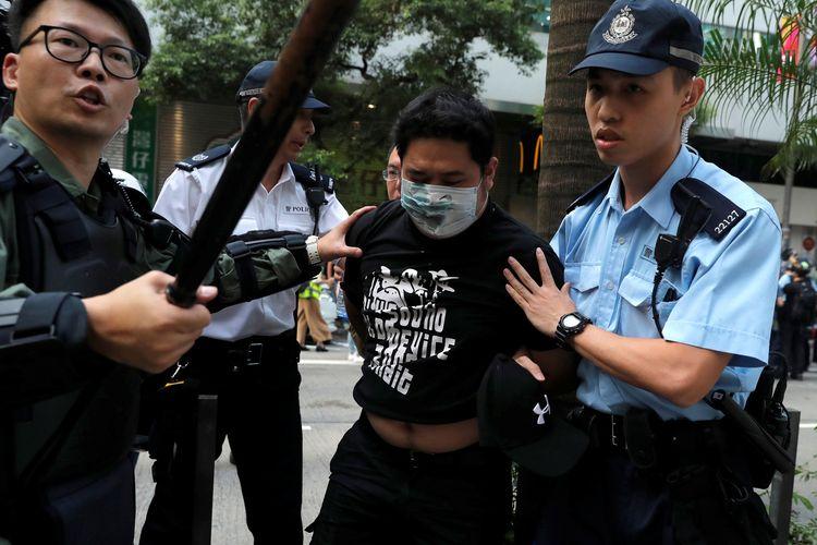 Seorang pria dikawal polisi saat pengunjuk rasa anti pemerintah dan demonstran pro China bentrok di distrik Wan Chai, saat Hari Nasional China, di Hong Kong, China, Selasa (1/10/2019).