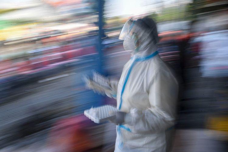 Seorang tenaga kesehatan yang mengenakan alat pelindung diri lengkap membawa sample tes usap (swab test) COVID-19 milik warga di kawasan Pasar Keputran, Surabaya, Jawa Timur, Kamis (17/9/2020). Pemerintah Kota Surabaya menyediakan 500 kuota tes usap secara gratis bagi warga Surabaya yang melintas di kawasan tersebut. ANTARA FOTO/M Risyal Hidayat/nz