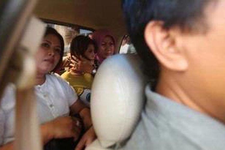 Novi Amalia (berkaus kuning) dipindahkan dari Polsek Metro Tamansari hendak dibawa ke Rs Polri untuk diperiksa kejiwaannya, Jakarta, Jumat (12/10/2012). Pada kamis (9/10/2012) sore, Novi yang mengendarai Honda Jazz warna merah menabrak sejumlah warga sipil dan polisi lalu lintas di Jalan Gajah Mada.