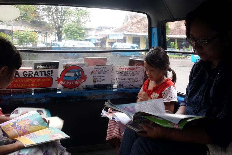 Seorang penumpang dan anak - anak saat baca buku di dalam angkot milik Sugiarto di Terminal Landungsari, Kota Malang, Senin (17/4/2017)