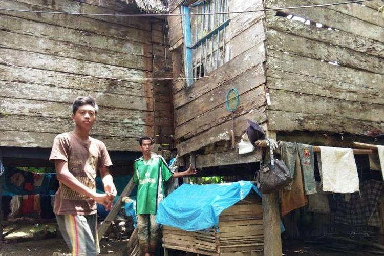 Zulfikri (14), ditemani orang tuanya Asmuzi (45) berada di halaman rumah panggung di Desa Desa Ampeh, Kecamatan Tanah Luas, Aceh Utara, Jumat (6/9/2019).