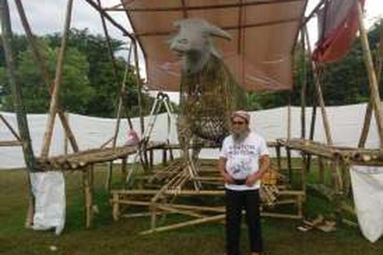 Sutradara seni kejadian Upacara Kebo Ketan, Bramantyo Prijosusilo, berpose di depan Kebo Ketan rancangannya.