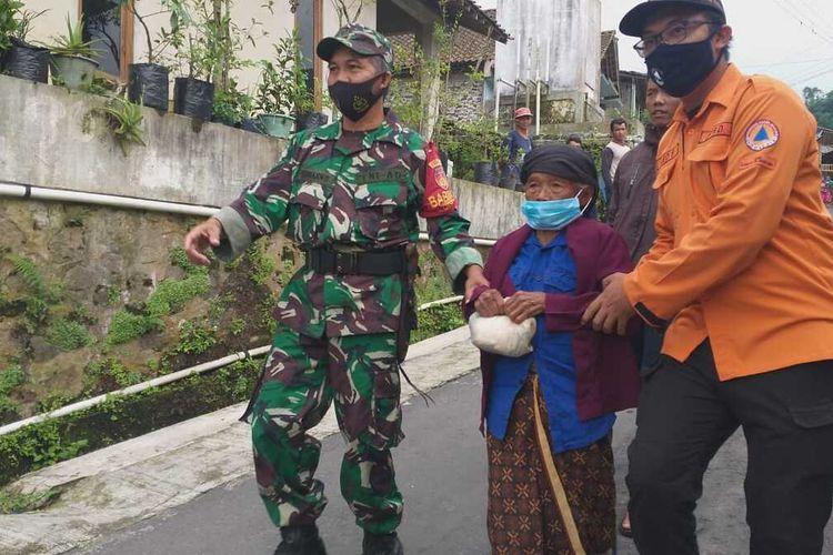 Anggota TNI dan BPBD Kabupaten Magelang menolong seorang lansia asal Dusun Babadan I, Desa Patena, Kecamatan Dukun, yang hendak dievakuasi ke TEA di Desa Banyurojo, Kecamatan Mertoyudan, Selasa (5/1/2021). Warga dievakuasi karena aktvitas Gunung Merapi meningkat.