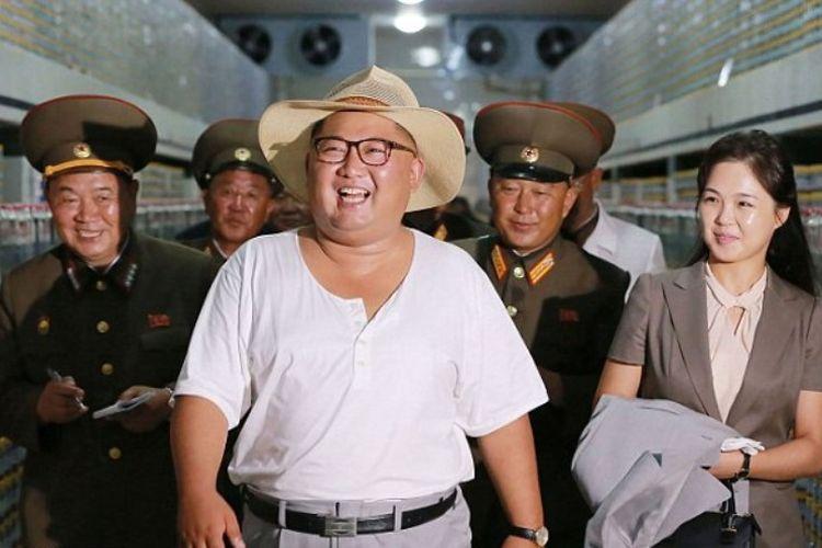 Gambar ini dirilis pada Rabu (8/8/2018) oleh kantor berita resmi Korea Utara (KCNA) menunjukkan pemimpin Korea Utara Kim Jong Un ditemani istrinya Ri Sol Ju mengunjungi  Pabrik Ikan Kumsanpho di Hwanghae Selatan Provinsi, Korea Utara. (AFP/KCNA via KNS)