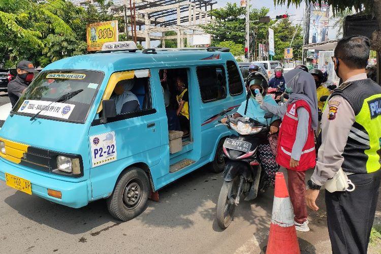 Seorang polisi memantau jalannya pemeriksaan suhu tubuh oleh petugas medis kepada pengendara yang melintas di posko check point Jalan Jendral Sudirman, Kota Tegal, Jawa Tengah, Rabu (23/4/2020).