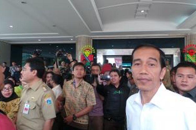 Gubernur DKI Jakarta Joko Widodo (kanan) memberikan santunan kepada warga dan memantau pasar murah yang diselenggarakan di kantor Wali Kota Jakarta Utara, Rabu (24/7/2013).