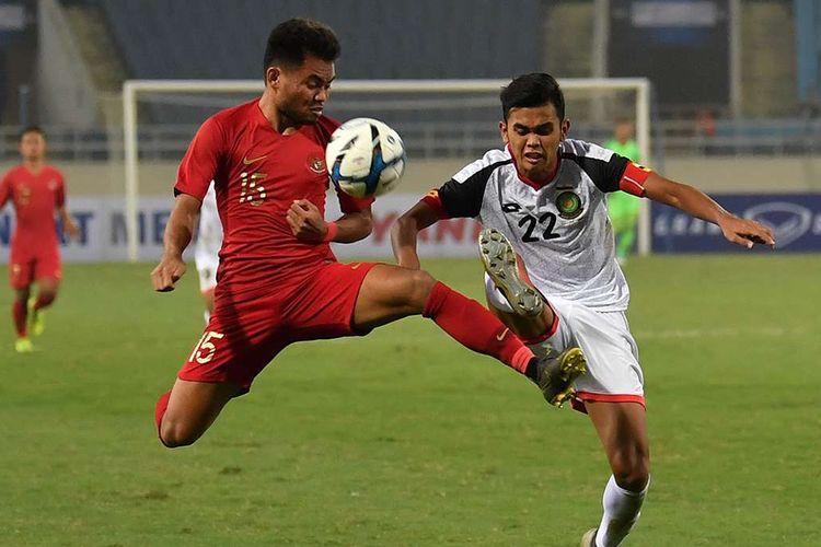 Pesepak bola tim nasional Indonesia U-23 Saddil Ramdani (kiri) berebut bola dengan pesepak bola tim nasional Brunei Darussalam U-23 Muhammad Hanif Hamir (kanan) pada pertandingan Grup K kualifikasi Piala Asia U-23 AFC 2020 di Stadion Nasional My Dinh, Hanoi, Vietnam, Selasa (26/3/2019). Tim nasional Indonesia U-23 mengalahkan tim nasional Brunei Darussalam U-23 dengan skor 2-1.