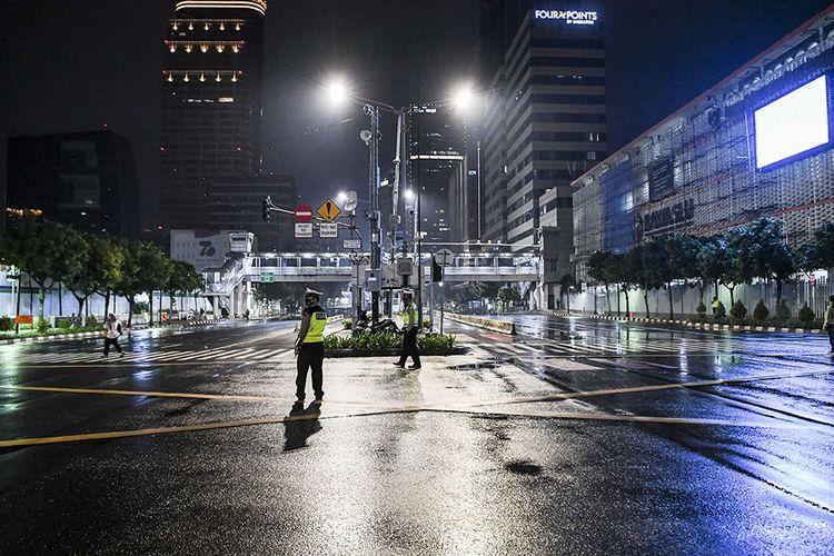 Petugas kepolisian berjaga saat diberlakukannya Car Free Night (malam bebas kendaraan)  dan Crowd Free Night (malam bebas keramaian) pada malam pergantian tahun di Jalan MH Thamrin, Jakarta (31/12/2020). Polda Metro Jaya melakukan  Car Free Night dan Crowd Free Night dengan menutup sepanjang Jalan Sudirman-MH Thamrin, Jakarta pada malam pergantian tahun untuk mencegah kerumunan warga.