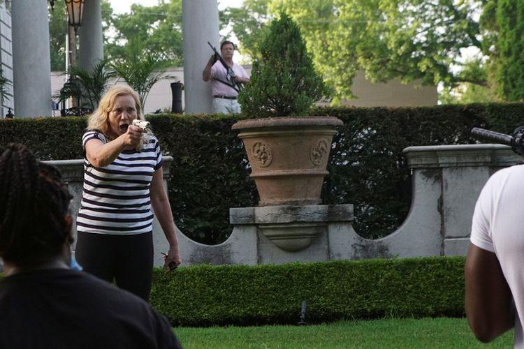 Seorang perempuan menodongkan pistol ke arah pengunjuk rasa yang hendak memasuki rumahnya dalam aksi menentang Wali Kota St Louis, Lyda Krewson, Missouri, Amerika Serikat (AS), pada 28 Juni 2020.