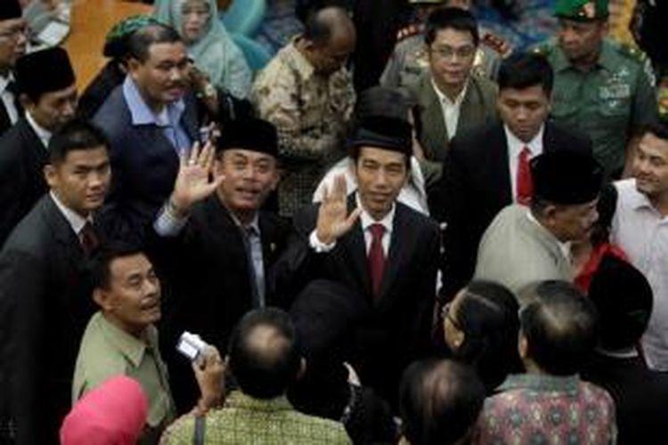 Presiden terpilih sekaligus Gubernur DKI Jakarta, Joko Widodo melambaikan tangan usai menghadiri rapat paripurna dengan agenda pandangan fraksi-fraksi di DPRD DKI Jakarta terhadap pengunduran dirinya di Gedung DPRD DKI Jakarta, Senin (6/10/2014).