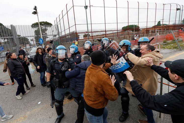 Bentrok para kerabat tahanan dengan polisi di luar Penjara Rebibbia, setelah larangan kunjungan diberlakukan untuk upaya pencegahan penyebaran virus corona di Roma, Italia, Senin (9/3/2020).