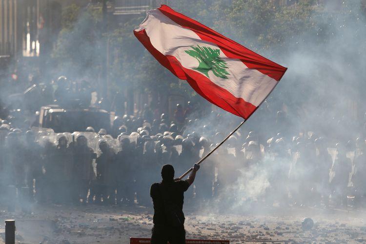 Seorang demonstran mengibarkan bendera Lebanon di depan pasukan polisi, dalam aksi unjuk rasa di Beirut, Lebanon, pada Sabtu (8/8/2020).