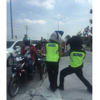 Dua polisi menghibur para pengendara yang melintas di kawasan Tol Fungsional Solo-Kertosono