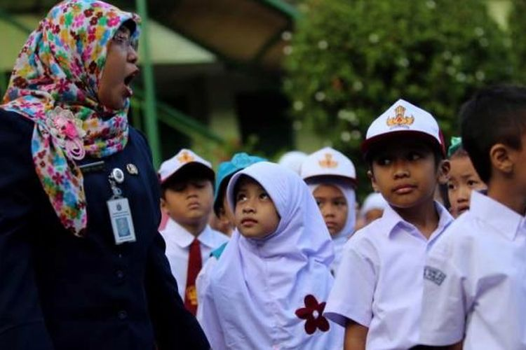 Anak-anak berbaris mengikuti upacara bendera pada hari pertama masuk sekolah di SDN 01 Menteng, Jakarta Pusat, Senin (18/7/2016).  Peraturan Menteri Pendidikan dan Kebudayaan Nomor 23 Tahun 2015 tentang Penumbuhan Budi Pekerti berisi, antara lain, tentang keterlibatan orangtua dalam pendidikan anak. Salah satu hal yang ditekankan ialah kewajiban orangtua mengantar anak ke sekolah pada hari pertama tahun ajaran baru.