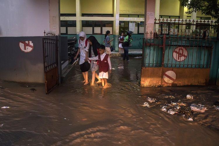 Warga melintasi genangan banjir bandang di SDN 224, Sukup Baru, Ujungberung, Bandung, Jawa Barat, Senin (1/4/2019). Banjir tersebut terjadi karena meluapnya Kali Cicalobak saat intensitas curah hujan yang tinggi yang merusak tanggul sehingga merendam sejumlah pemukiman warga serta merusak sebuah sebuah sekolah dasar. ANTARA FOTO/Novrian Arbi/foc.